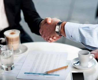 Business handshake over a coffee